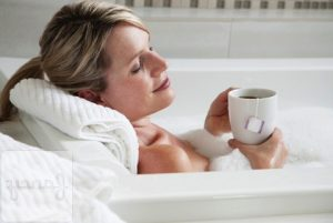 Woman drinking tea in the bath --- Image by ゥ Marnie Burkhart/Corbis