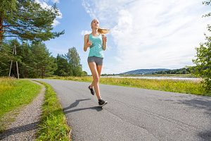 Motivated woman runs fast on a road in the forest