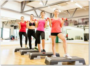 fitness, sport, training, gym and lifestyle concept - group of smiling female with dumbbells and aerobic step