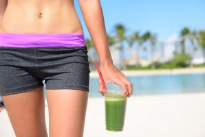 Green vegetable smoothie. Woman living healthy lifestyle drinking vegetable smoothies after fitness running workout on summer day. Beautiful fit sports model eating healthy.
