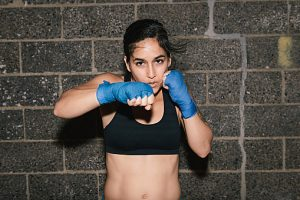 A young brunette woman exercising and boxing punching towards the camera