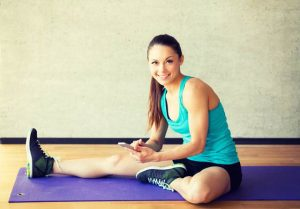 34718258 - fitness, sport, training and lifestyle concept - smiling woman stretching leg on mat in gym
