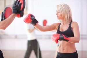 Young woman and trainer boxing in gym