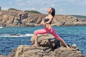 young brunette woman doing yoga on rocky coastline