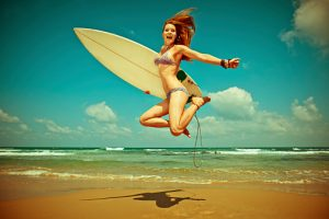 Young woman jumping with surf-board on the beach