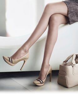 Female legs with shoes and handbag.