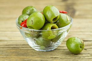 Glass bowl of marinated green olives on wood