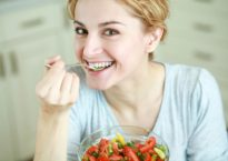 An image of a woman eating vegetable salad