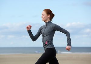 Smiling woman jogging at the sea side