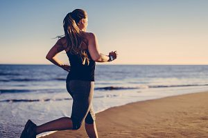 Woman jogging at beach with smartwatch.