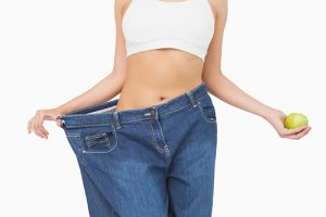 Mid section of slim woman wearing too big jeans holding an apple