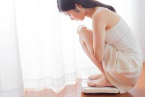 体重計に乗る女性、ダイエット、美容、覗き込む